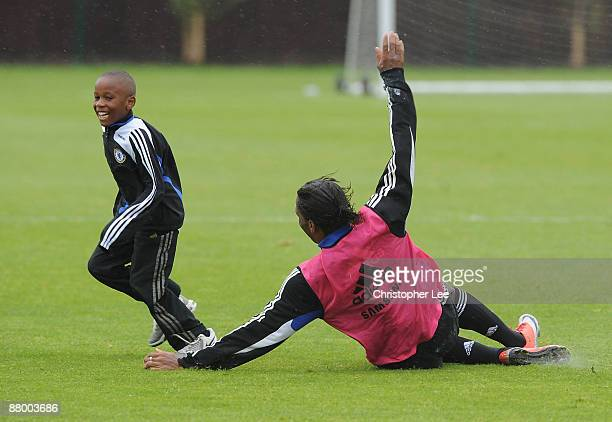 Didier Drogba tries to tackle a young kid as they play around during the Chelsea Football Club Training Session held at their Cobham Training Ground...
