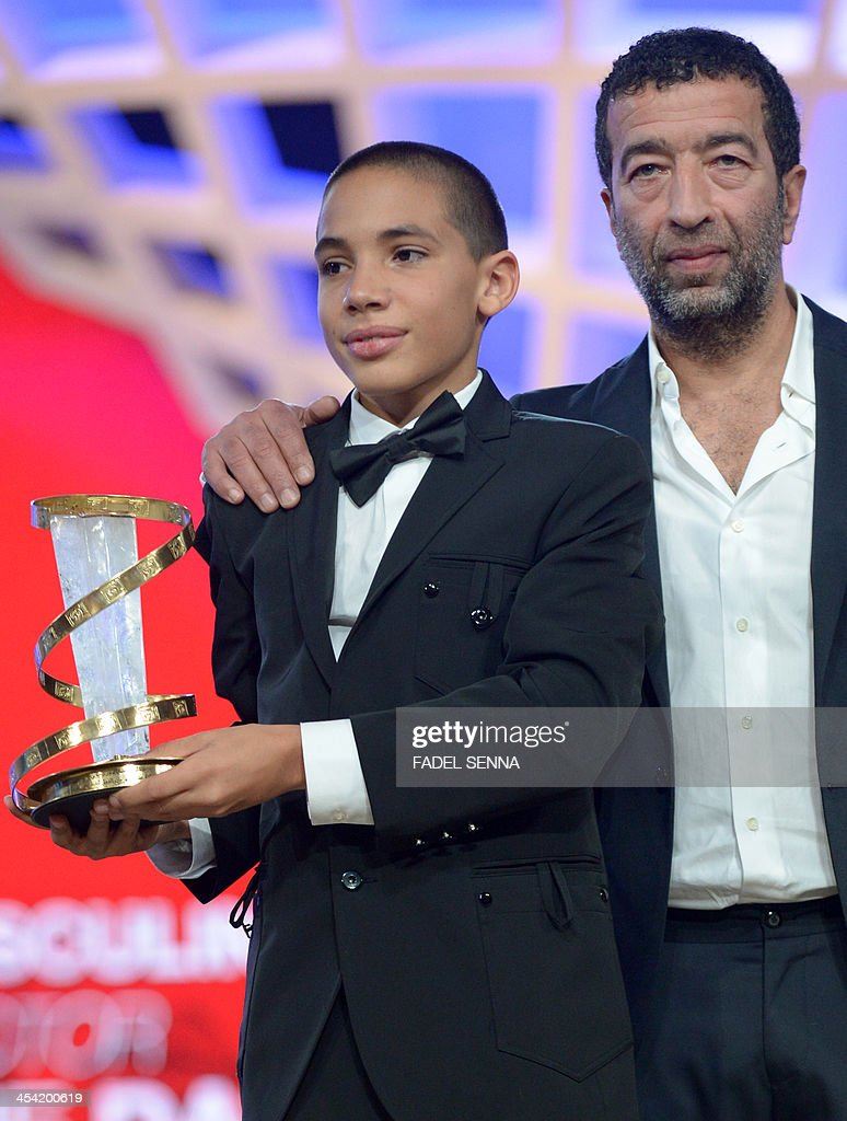 Didier Michon and Slimane Dazi hold the prize of the best performance by an actor during the closing ceremony of the 13th Marrakech International Film Festival on December 7, 2013 in Marrakech.