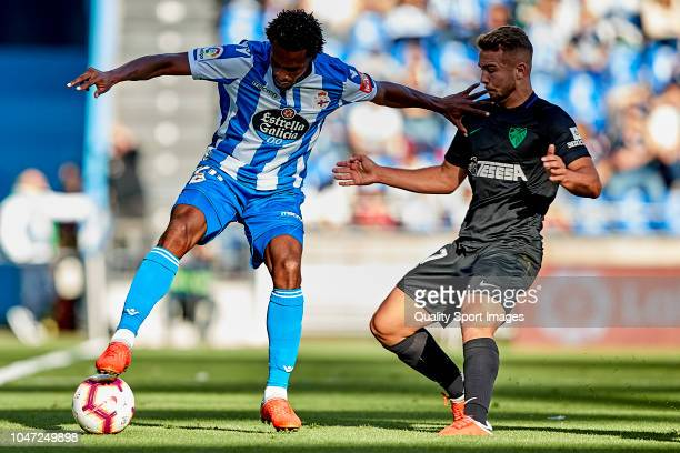 Didier Moreno of Deportivo de La Coruna is challenged by Javier Ontiveros of Malaga CF during the La Liga 123 match between Deportigo de La Coruna...