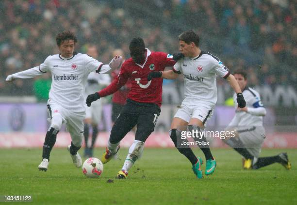 Didier Ya Konan of Hannover and Takashi Inui and Stefano Celozzi of Frankfurt compete for the ball during the Bundesliga match between Hannover 96...
