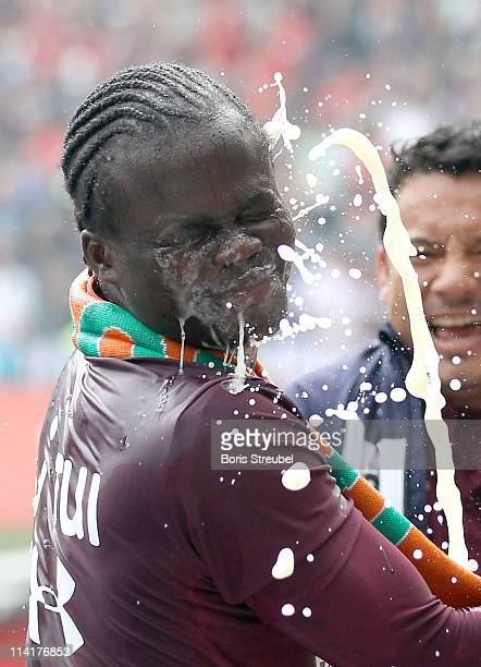 Didier Ya Konan of Hannover gets a champagne shower after the Bundesliga match between Hannover 96 and 1 FC Nuernberg at AWD Arena on May 14 2011 in...