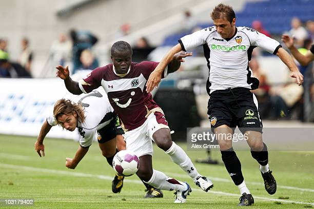 Didier Ya Konan of Hannover is challenged by Alexis Ruano Delgado and Joaquin Sanchez Rodriguez of Valencia during the preseason friendly match...