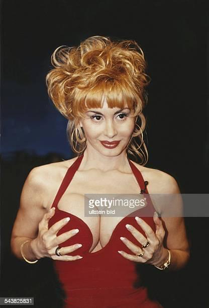 Die aus Prag stammende Pornodarstellerin sowie PornoProduzentin Dolly Buster trägt ein rotes Oberteil mit tiefem Ausschnitt An einem Träger der um...