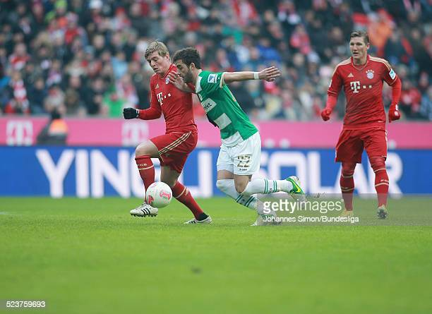 Die BayernSpieler Toni Kroos und Bastian Schweinsteiger und der Fuerther Thanos Petsos kaempfen um den Ball beim Bundesligaspiel FC Bayern Muenchen...