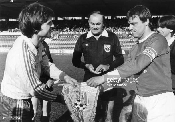 Die beiden Kapitäne Ronald Worm von Eintracht Braunschweig und Rüdiger Schnuphase von Rot-Weiß Erfurt tauschen am 8.4.1985 vor einem...