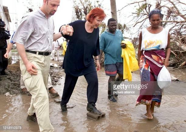 Die deutsche Entwicklungshilfeministerin Heidemarie WieczorekZeul muß am 1232000 auf ihrem Weg zum zerstörten Hospital von Machanga durch Wasser und...