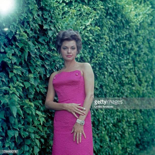 Die deutsche Schasuspielerin Nadja Tiller in einem rosa Kleid an einer Hecke Italien 1960er Jahre