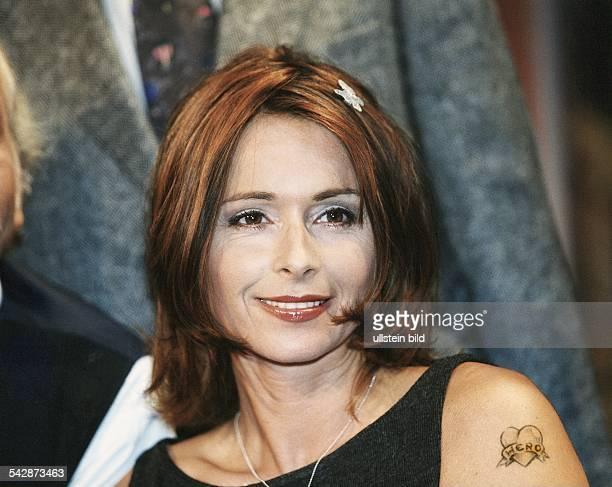 Die deutsche Schauspielerin Christina Plate trägt als Haarspange einen glitzernden Schmetterling und auf der Schulter eine Tätowierung ein Herz auf...