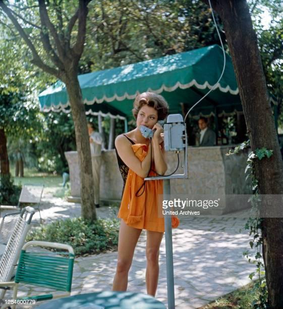 Die deutsche Schauspielerin Nadja Tiller am Telefon beim Hotel Swimmingpool, Italien 1960er Jahre.