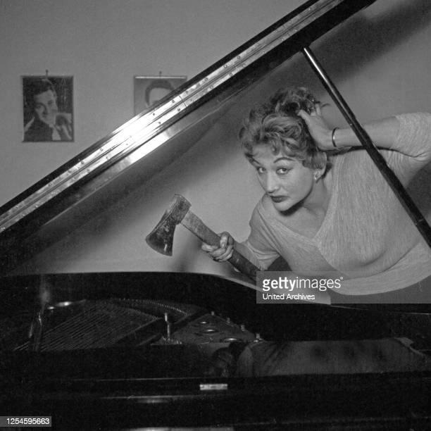 Die deutsche Sängerin Schauspielerin und Tänzerin Evelyn Künneke am Flügel mit einer Axt Deutschland 1956