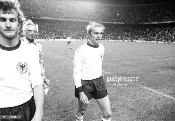Die deutsche Spieler Rainer Bonhof und Erich Beer verlassen mit Betreuer Heinz Dahn bei Spielende zufrieden das Feld. Die deutsche...