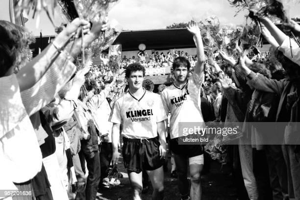 Die Dresdner Spieler HansUwe Pilz und Andreas Trautmann gehen durch ein Blumenspalier gebildet von Dresdner Fans 45000 DynamoFans feiern am im...