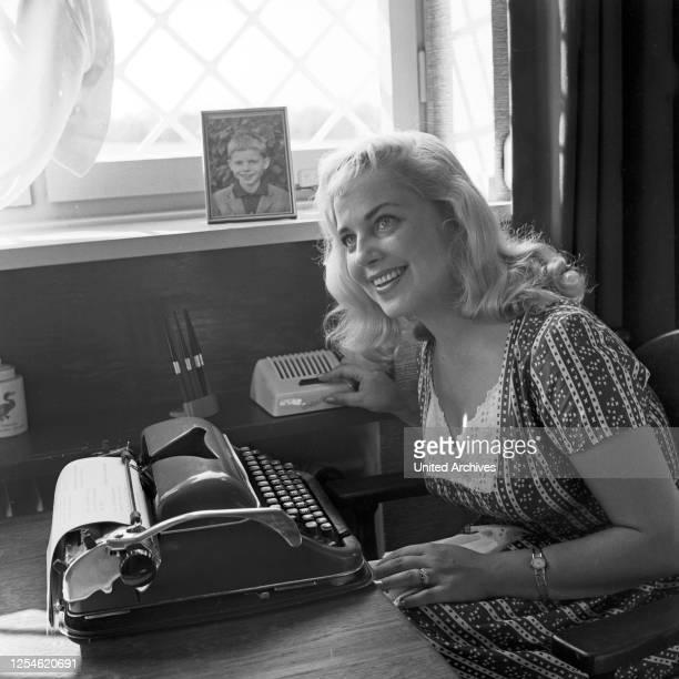Die Ehefrau von Peter Frankenfeld, Lonny Kellner als Sekretärin an der Schreibmaschine und an einer Gegensprechanlage, Deutschland 1960er Jahre.
