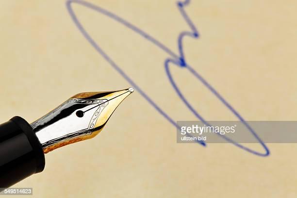 Die Feder eines Füllhalters und eine Unterschrift Symbolisch für Verträge Testament und Unterzeichnung