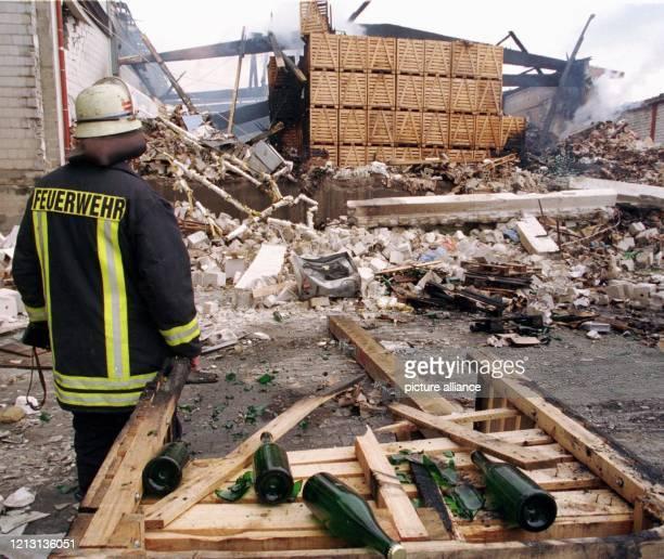 Die Feuerwehr löscht am 2452000 letzte Brandherde auf dem Gelände in Grünstadt Eine Explosion hatte hier eine Lagerhalle für Spirituosen zerstört und...