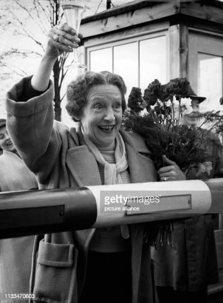 Die Filmschauspielerin Henny Porten mit einem Glas Sekt und einem Strauß roter Rosen im Arm am Schlagbaum des Zonengrenzkontrollpunktes BerlinStaaken...