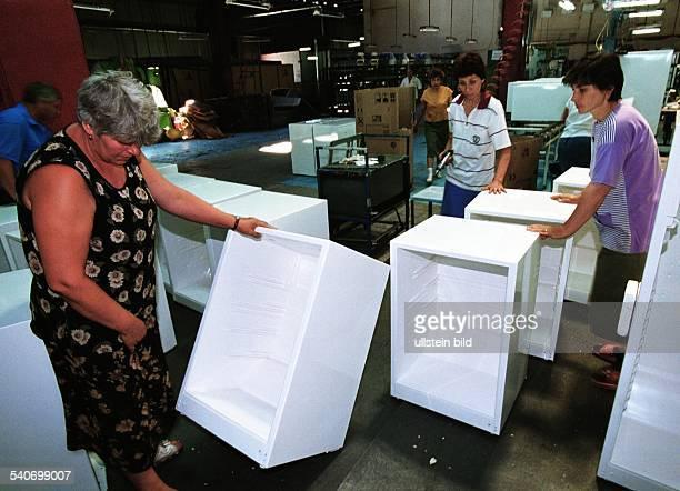 Die Firma Arctic SA stellt Kühlschränke in Rumänien her Arbeiterinnen begutachten die Kühlschrankgehäuse und transportieren sie durch eine Werkhalle