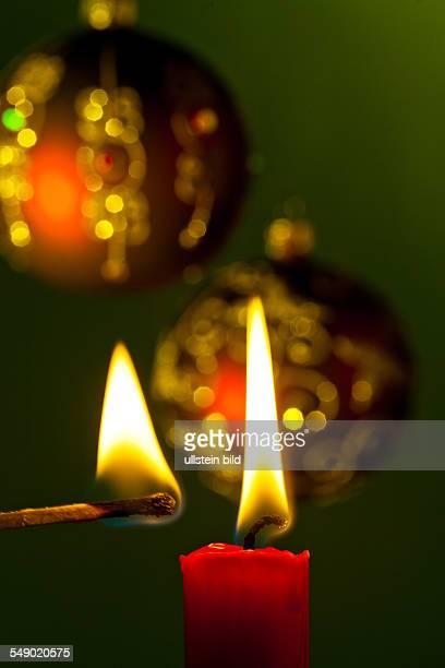 Die Flamme einer Kerze bringt Licht in die Dunkelheit Mit Weihnachtskugeln