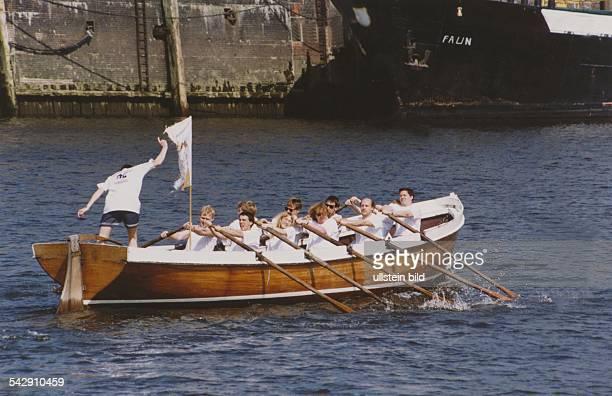 Die gemischte Mannschaft der Fachhochschule Hamburg trainiert auf der Elbe nahe beim Fischereihafen Die Ruderer des kutterartigen Bootes legen sich...
