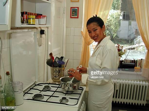 Die Generalkonsulin von Honduras Patricia Rivera Rodil beim Kochen an einem Gasherd Bekleidet mit einer weißen Schürze würzt sie das Gericht in einem...