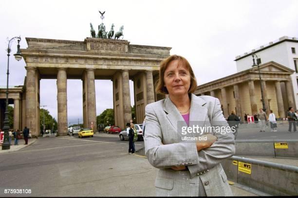 Die Generalsekretärin der CDU Dr. Angela Merkel steht mit verschränkten Armen vor dem Brandenburger Tor. .