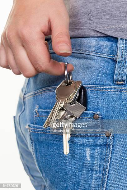 Die Hand einer jungen Frau in Jeans mit Schlüsselbund Schlüssel für Auto und Wohnung