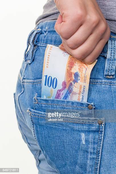 Die Hand einer jungen Frau zieht einen Schweizer Franken Geldschein aus der Tasche ihrer Jeans