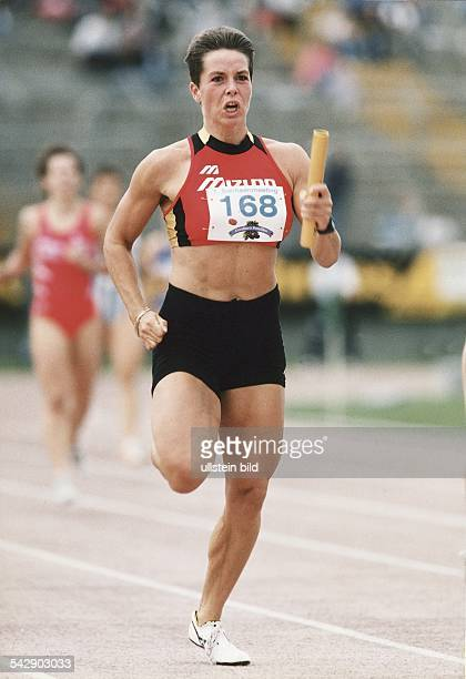 Die Mittelstreckenläuferin Grit Breuer mit dem Staffelholz in der Hand