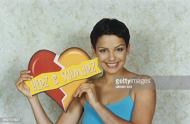 Die Moderatorin Andrea Wieser hält das Logo ihrer Sendung 'Herz Schmerz' hoch Aufgenommen Mai 2000