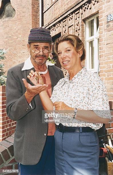 Die Schauspieler Walter Giller und Evelyn Hamann bei Dreharbeiten vor einem Haus Giller trägt Mütze und Brille Hamann läßt einen Schlüssel in die...