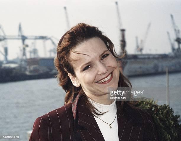 Die Schauspielerin Andrea Kathrin Loewig lächelt mit leicht geneigtem Kopf Ihre Haare sind mit einem Tuch zurückgebunden Im Hintergrund ein...