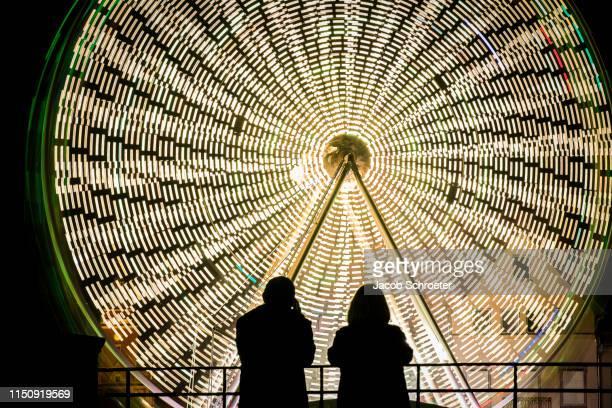 die silhouette von zwei personen vor einem riesenrad. - zwei personen stock pictures, royalty-free photos & images