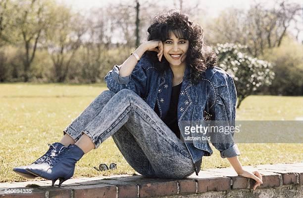 Die Sängerin Ofra Haza sitzt mit angezogenen Beinen auf einer Mauer und lehnt ihre Hand an ihren Kopf Sie trägt einen blauen Jeansanzug mit...