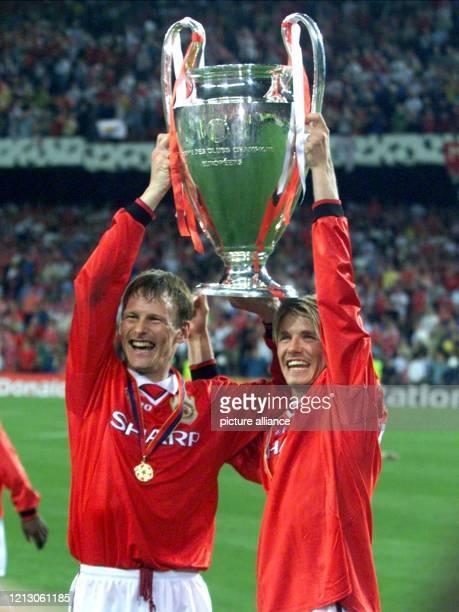 Die Spieler Teddy Sheringham und David Beckham von Manchester United halten am nach dem Sieg im Champions LeagueFinale über FC Bayern München jubelnd...