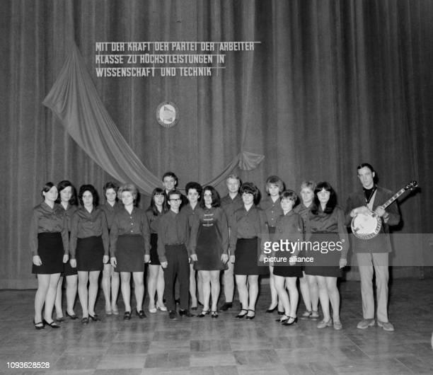 Die Studenten des RussischClubs der Universität Jena stehen auf der Bühne in der Aula am Auf der Bühne sieht man die Losung Mit der Kraft der Partei...
