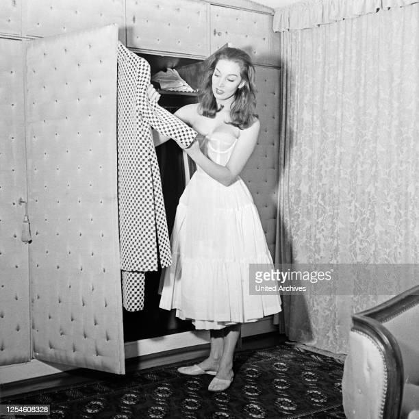 Die sucht sich aus dem Wandschrank ein passendes Kleid bei einem Fotoshooting im Schlafzimmer Deutschland 1950er Jahre