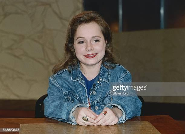 Die Theaterschauspielerin Christine Urspruch sitzt an einem Tisch und hat an beiden Händen je einen großen Ring mit Steinen An ihrer Jeansjacke ist...