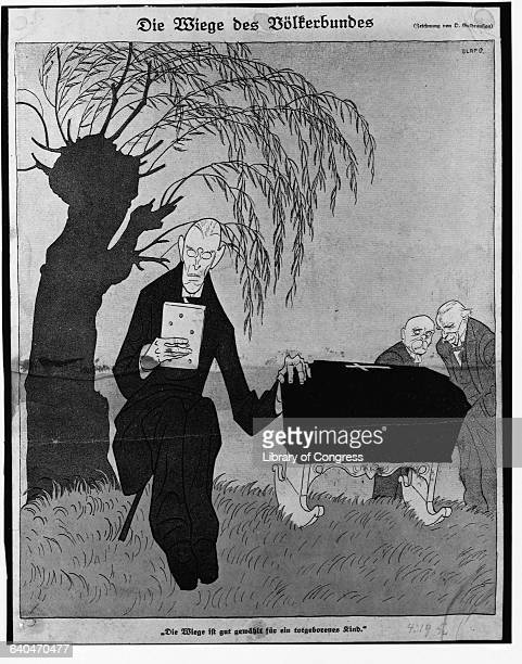 """""""Die Wiege des Volkerbundes."""" Political cartoon depicting Woodrow Wilson rocking a cradle that is a coffin, with Lloyd George and Georges Clemenceau..."""