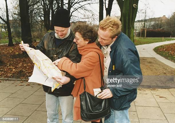 Diebstahl: Einer Frau, abgelenkt durch einen Stadtplan, wird aus der Handtasche ein Portemonnaie geklaut. Aufgenommen Februar 1995. Symbolbild