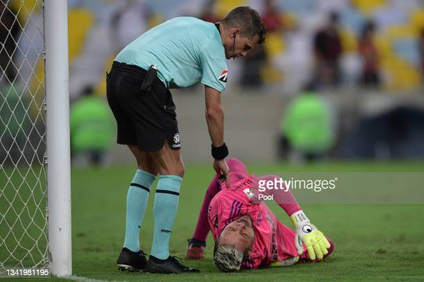Diego Alves of Flamengo reacts after suffering an injury as Referee Andrés Cunha assists him during a semi final first leg match between Flamengo and...
