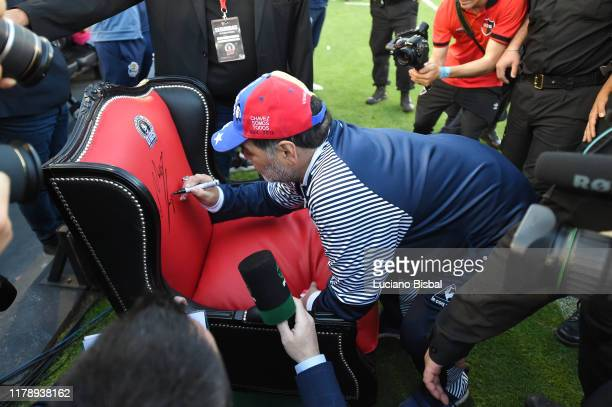 Diego Armando Maradona coach of Gimnasia signs the armchair that was previously given to him a match between Newell's Old Boys and Gimnasia y Esgrima...