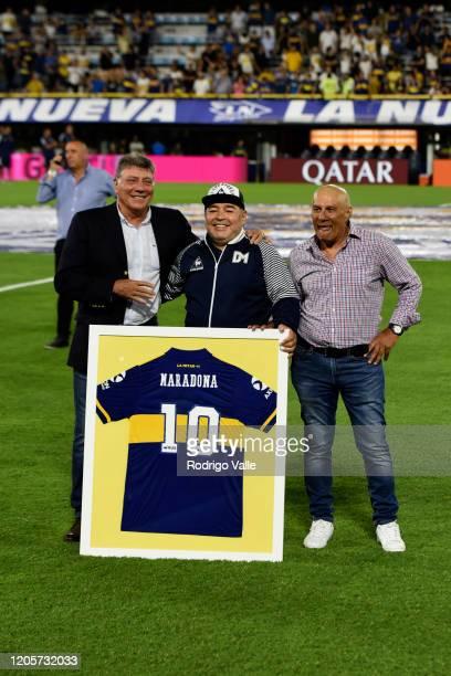 Diego Armando Maradona head coach of Gimnasia y Esgrima La Plata receives a Boca Juniors jersey from Hugo Perotti and Miguel Brindisi before a match...