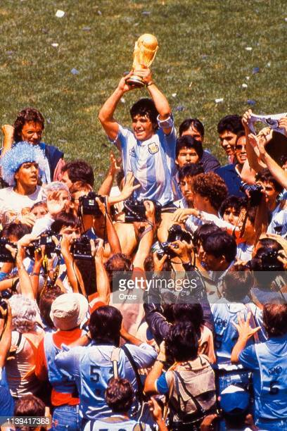 Diego Armando Maradona of Argentina celebrate his victory with the trophy during the World Cup Final match between Argentina and West Germany at...