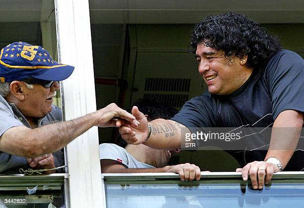 Diego Armando Maradona soccer star and former Boca Jrs player greets a fan before the start of Boca vs Nueva Chicago match 18 April 2004 in Buenos...