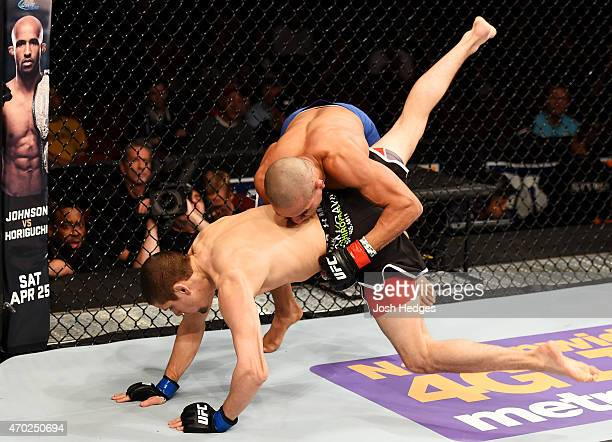 Diego Brandao takes down Jimy Hettes in their featherweight bout during the UFC Fight Night event at Prudential Center on April 18 2015 in Newark New...