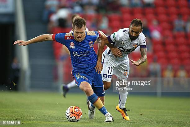 Diego Castro of the Glory contests the ball with Nigel Boogaard of the Jets during the round 25 ALeague match between the Newcastle Jets and the...