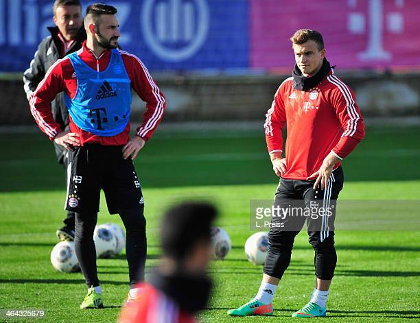 Diego Contento and Xherdan Shaqiri of Muenchen lok on during a training session of FC Bayern Muenchen on January 22 2014 in Munich Germany