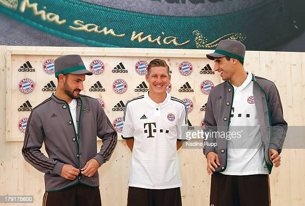 Diego Contento Bastian Schweinsteiger and Javi Martinez of FC Bayern Muenchen present their new trikot in bavarian style at Saebener Strasse training...