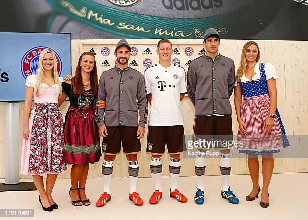 Diego Contento Bastian Schweinsteiger and Javi Martinez of FC Bayern Muenchen present their new trikot in bavarian style at Saebener Strasse training...