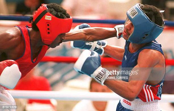 Diego Corrales of the US ducks a punch from Arnaldo Mesa Bonell of Cuba 18 March during featherweight boxing competition at the 12th Pan American...